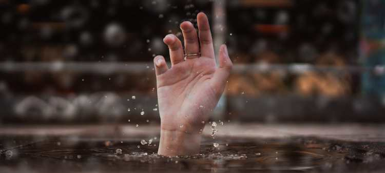 person's hand sticking out above surface of water