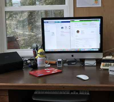monitor with bookkeeping apps open on wooden desk